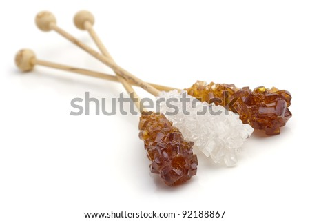 Candy brown and white sugar on a sticks. With white background. Soft focus. - stock photo