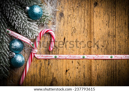 candy cane and christmas balls decoration on a wooden table - stock photo