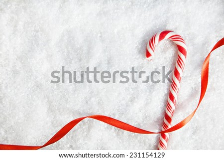 Candy Cane And Ribbon On Snowy Background. Copy Space - stock photo
