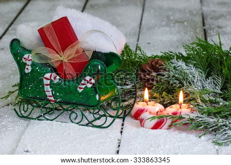 Candy cane candles, Santa Claus sleigh with stockings and presents by Christmas tree garland and snow