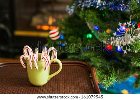 Candy cane candy in a mug against a Christmas Background - stock photo