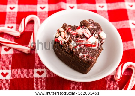 Candy cane fudge in heart shape sitting on festive red and white napkin