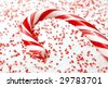 Candy Cane nestled in white and red sugar.  Macro with extremely shallow dof. Selective focus on end of candy cane. - stock photo
