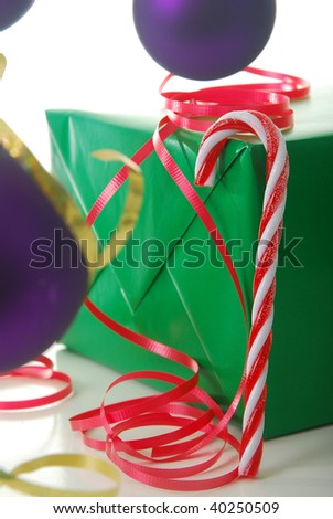 candy cane resting on present isolated on white, shallow depth of field. - stock photo