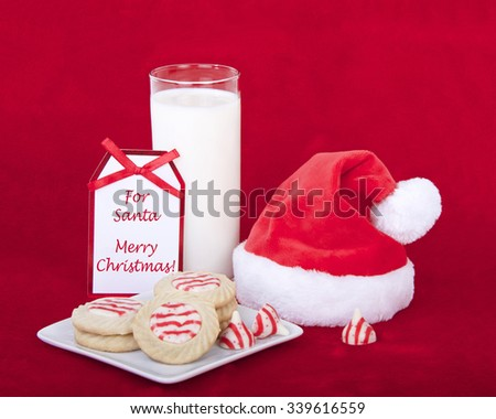 candy cane stripped peppermint flavor sugar cookies on a serving plate with a glass of milk and a miniature santa hat. Not card says For Santa Merry Christmas. Red fur background - stock photo