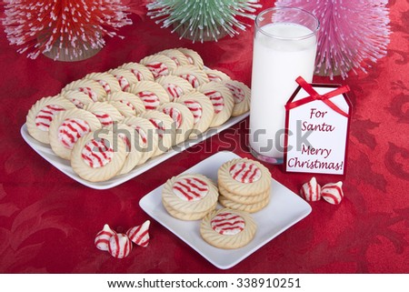 candy cane stripped peppermint flavor sugar cookies on a serving plate with cookies on a square plate for santa with a glass of milk. Note next to milk says For Santa Merry Christmas - stock photo