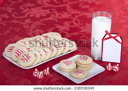 candy cane stripped peppermint flavor sugar cookies on a serving plate with cookies on a square plate for santa with a glass of milk. Note card blank for your message - stock photo