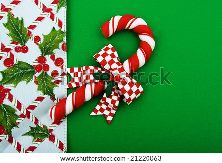 Candy cane with leaves and holly berries on green background, Christmas background - stock photo