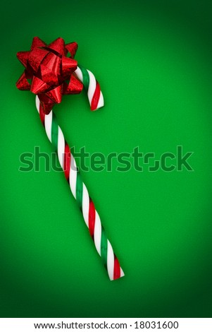 Candy cane with red bow on green background, candy cane