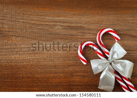candy canes and bow on weathered wooden board - stock photo