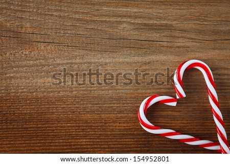 candy canes as heart on weathered wooden board - stock photo