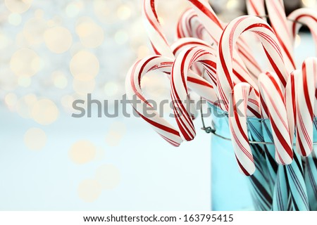 Candy canes in a pretty glass blue Container. Extreme shallow depth of field with selective focus on center candy. - stock photo