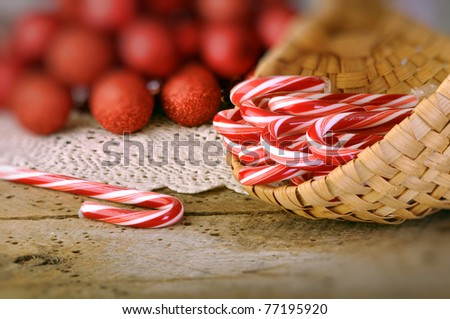 Candy canes in basket with Christmas balls in background on old vintage wood table - stock photo