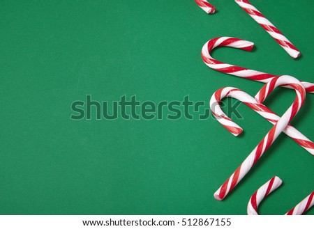 Candy canes on a green background with empty space at side forming a page border