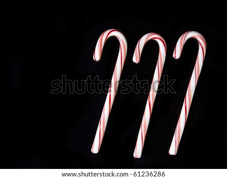Candy canes on black background isolated for your next project - stock photo