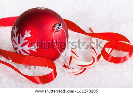 Candy canes with red Christmas ball ornament and ribbon on snow background