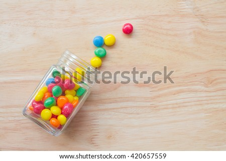 candy colorful in jar falling some candy outside jar  on wooden background