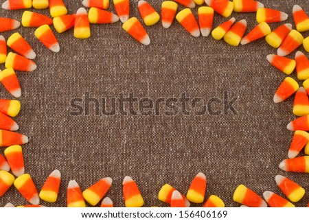 Candy Corn Framing Brown Tweed Fabric with center background space or room for your words, text, copy for Harvest Festival, Halloween or Thanksgiving - stock photo