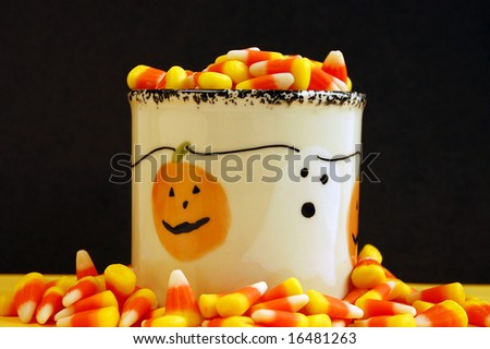 Candy corn in jar against black background - stock photo