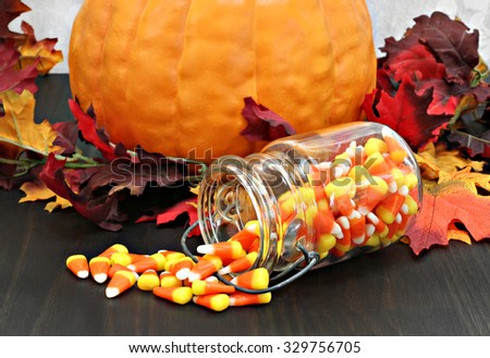 Candy corn spilling from an old mason jar onto a table that is decorated for fall. - stock photo