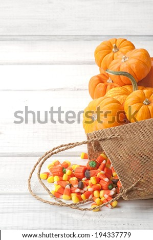 Candy Corn Spilling from Burlap Bag on Rustic White or Gray Wood Board Background with room or space for copy, text.  Vertical - stock photo