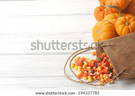 Candy Corn Spilling from Burlap Bag on Rustic White or Gray Wood Board Background with room or space for copy, text.   Horizontal - stock photo