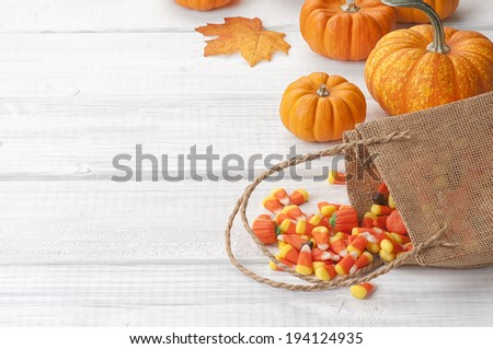 Candy Corn Spilling from Burlap Bag with mini pumpkins on Rustic White or Gray Wood Board Background with room or space for copy, text.  Horizontal - stock photo