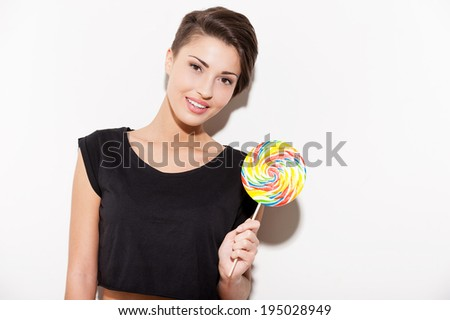 Candy girl. Attractive young short hair woman holding a big lollipop and smiling - stock photo