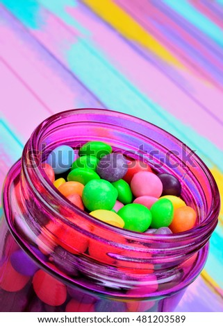 candy in pink jar on multicolor wooden table