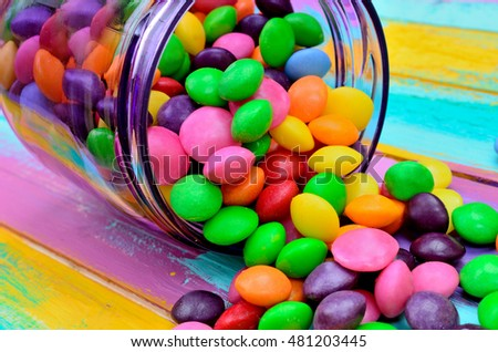 candy in purple jar flow on multicolored wooden table