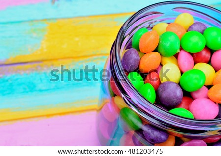 candy in purple jar on multicolored wooden table