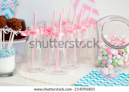 Candy jar and fancy milk bottles for drinks on a dessert table at party or wedding celebration - stock photo