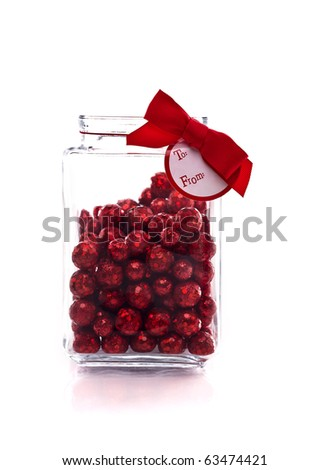 Candy jar with red glittery candy, and gift tag isolated on white with copy space