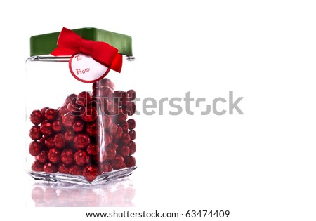 Candy jar with red glittery candy, green lid and gift tag isolated on white with copy space - stock photo