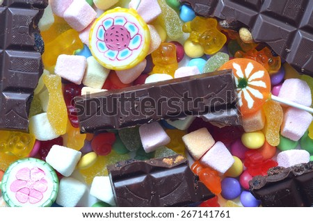 Candy, lollipop, chocolate, colored smarties and gummy bears background - stock photo
