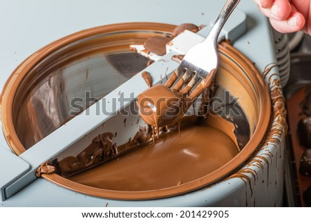 Candy maker using a chocolate coating machine to make candy - stock photo