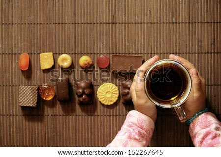 candy set for tea, and a little girl - stock photo
