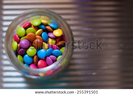 candy shell coated chocolate beans in a glass jar - stock photo