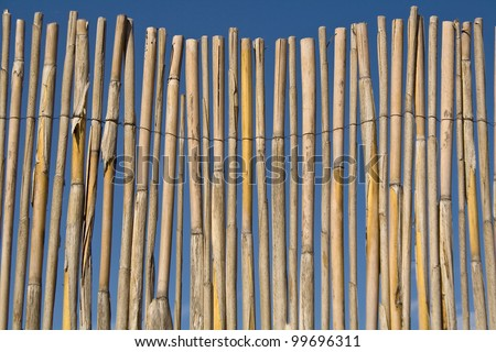 Cane fence texture over blue sky - stock photo