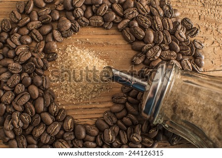 Cane granulated Sugar bowl lie on round coffee beans Old retro vintage aged wooden board table  - stock photo