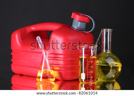 canister and fuel in test tubes on black background - stock photo