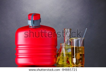 canister and fuel in test tubes on gray background - stock photo