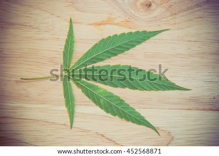 cannabis leaf on old wooden table - stock photo