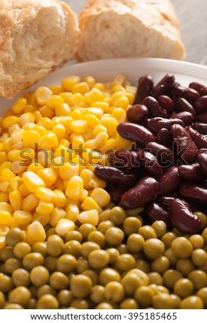 Canned corn, beans and peas in a white plate with white bread, selective focus, closeup, vertical - stock photo