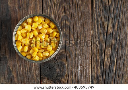 Canned corn in an iron jar on wooden background, top view - stock photo