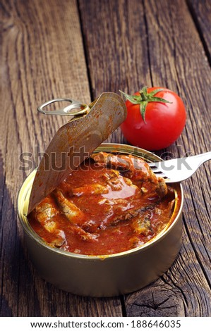Canned fish in tomato sauce on old wooden table - stock photo