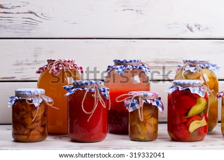 Canned food on old wooden shelves. Harvesting products for the winter. - stock photo