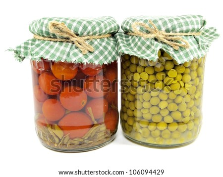 canned green peas and tomatoes in glass jars on a white background - stock photo