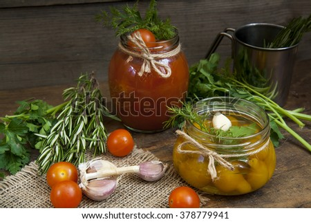 Canned marinated tomatoes in tomato juice on a wooden table - stock photo
