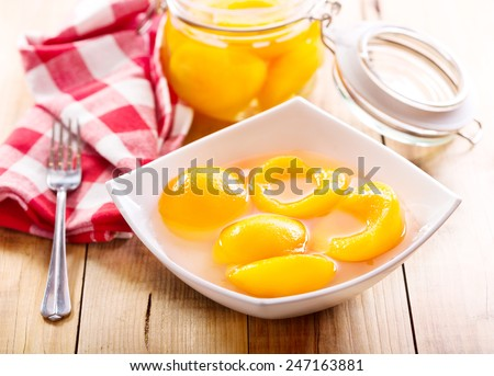 canned peaches in a bowl on wooden table - stock photo